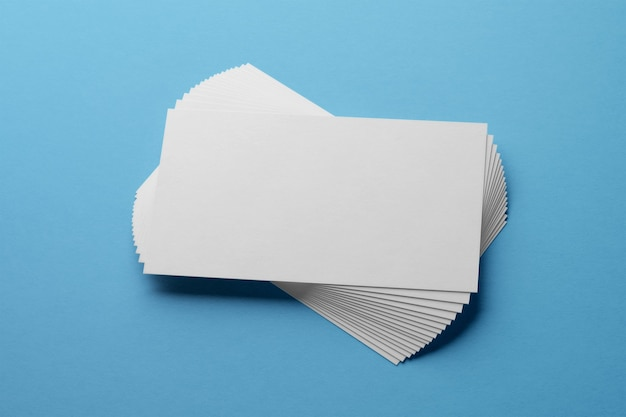 Mockup of white business cards fan stack at blue textured paper