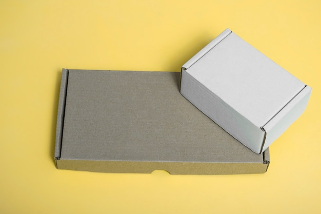 Mockup of white cardboard box and brown cardboard box on yellow background place for text form
