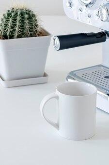 커피 머신과 세로보기에 흰색 테이블에 선인장 모형 화이트 세라믹 머그잔.