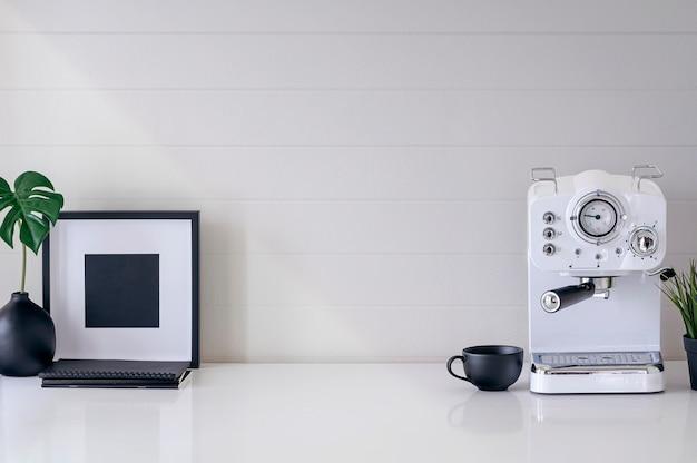 Макет белая кофеварка, чашка, деревянный каркас и комнатное растение на белом столе с копией пространства.