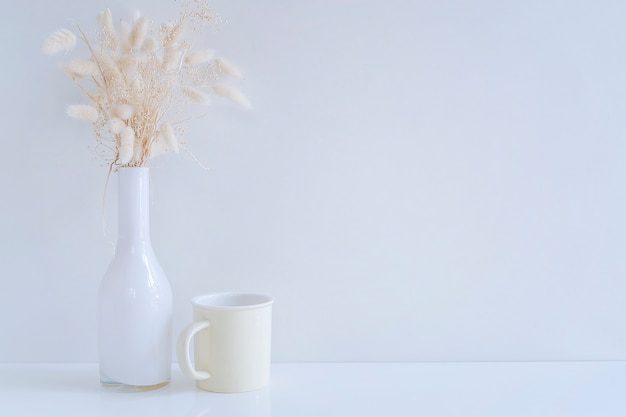 Mockup white glass vase with hay flower and yellow mug on white table