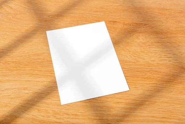 창에서 추상적인 빛과 나무 테이블 배경에 흉내낸 흰색 인사말 종이 카드.