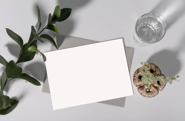 봉투와 녹색 잎이 있는 흰색 연하장 카드입니다. 목업 디자인 템플릿입니다.
