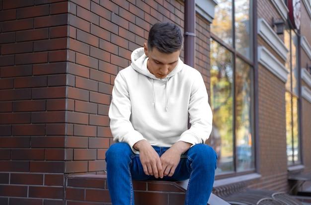 通り、正面図の若い男のモックアップ白いパーカー。あなたのデザインとパターンで、店でプレゼンテーションするためのファッションデザイン。袖付きのカジュアルな服のテンプレート。