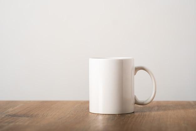 ミニマリストのスカンジナビアのインテリアの木製のテーブルトップに白いマグカップをモックアップします。テンプレート、デザインのレイアウト、広告、コピースペース付きのロゴ。カップライトベージュの背景