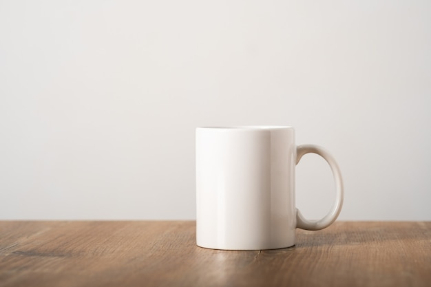 Mockup white mug on a wooden table top in a minimalist scandinavian interior. template, layout for your design, advertising, logo with copy space. cup light beige background