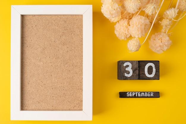 Макет белой фоторамки сухой цветок с деревянным календарем дата 30 сентября на деревянном календаре