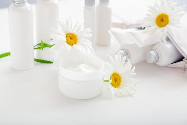 모이스처라이저 스킨 크림, 흰색 바탕에 로션을 위한 흰색 플라스틱 항아리. 카모마일 꽃과 함께 흰색 항아리에 모이스처 라이저 스킨 크림. 튜브와 병에 흰색 피부 관리 제품 세트.