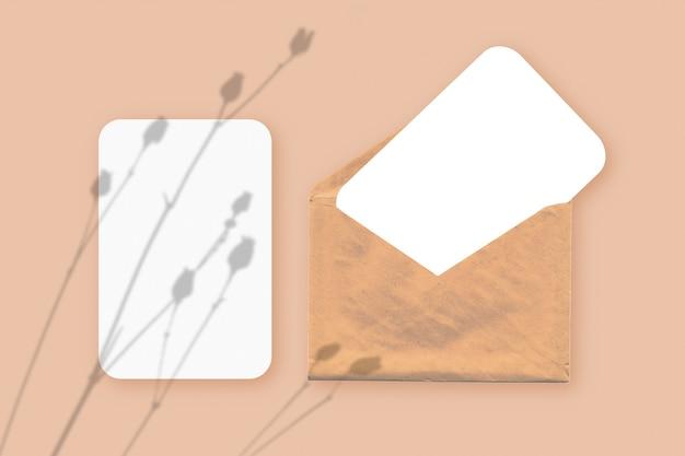 Мокап с наложением теней растений на конверт с двумя листами текстурированной белой бумаги на бежевом фоне стола. горизонтальная ориентация.