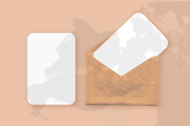 주황색 테이블 배경에 질감 있는 흰색 종이 두 장이 있는 봉투에 식물 그림자가 오버레이된 모형입니다. 수평 방향.
