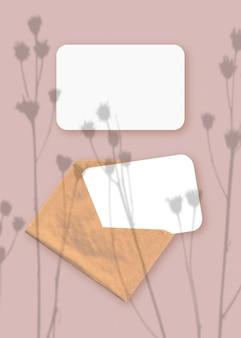 분홍색 테이블 배경에 질감 있는 흰색 종이 두 장이 있는 봉투에 식물 그림자가 오버레이된 모형입니다. 수직 방향.
