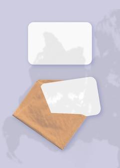 보라색 테이블 배경에 질감 있는 흰색 종이 두 장이 있는 봉투에 식물 그림자가 오버레이된 모형입니다. 수직 방향.