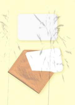 Макет с наложением теней растений на конверт с двумя листами текстурированной белой бумаги на желтом фоне стола. вертикальная ориентация.