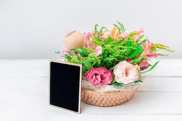 Макет с красивым букетом цветов и черной пустой доской на фоне белого стола с копией пространства