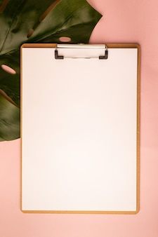 Mockup with clipboard and monstera leaf on pink background. flat lay, top view, copy space.
