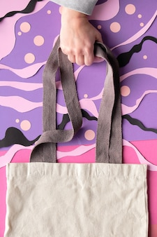 Mockup with copy-space. hand holds canvas bag on abstract sea underwater background
