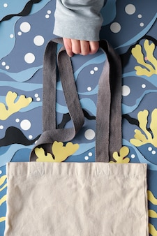 복사 공간이있는 모형. 손을 잘라 종이에서 추상 바다 수중 배경에 캔버스 가방을 보유
