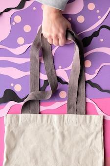 복사 공간이있는 모형. 손 추상 바다 수 중 배경에 캔버스 가방을 보유