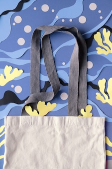 Mockup with copy-space for your design. blank canvas bag on underwater background from cut paper