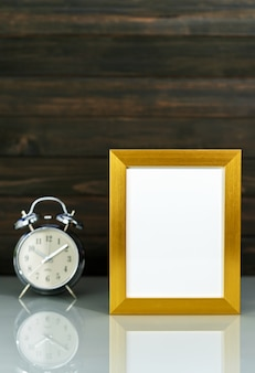 Mockup with golden frame and alarm clock