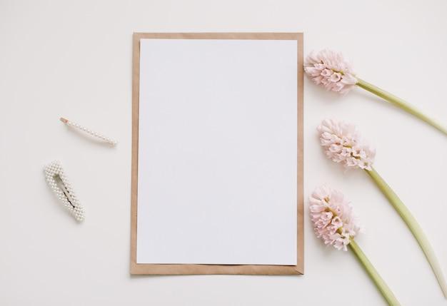 핑크 꽃과 복사 공간을 가진 빈 종이 이랑.