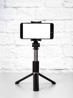 Mockup with smartphone on a tripod with empty screen