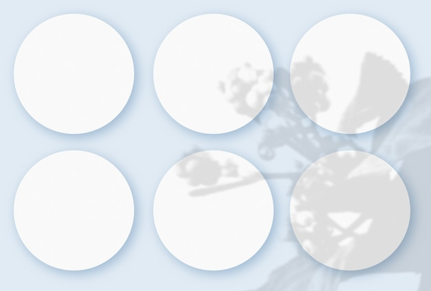 Mockup with vegetable shadows superimposed on 6 round sheets of textured white paper on a blue table background