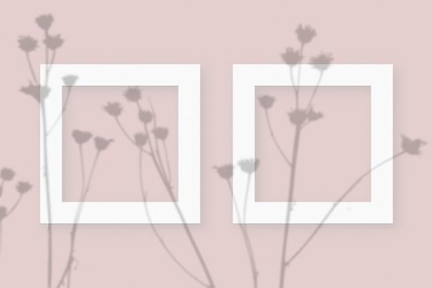 ピンクのテーブルの背景にテクスチャの白い紙の2つの正方形のフレームに野菜の影を重ねたモックアップ。