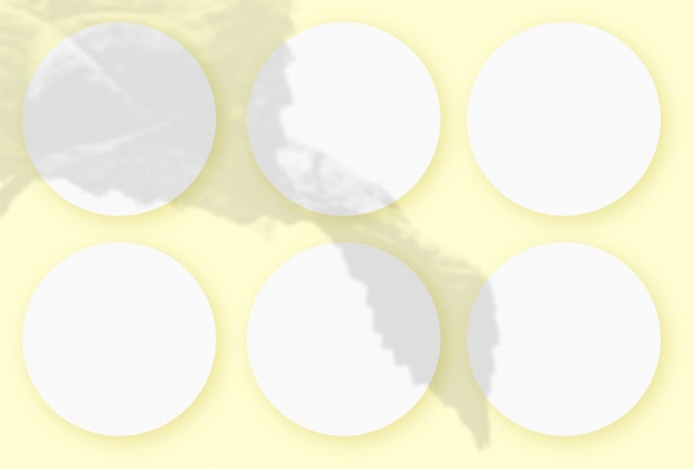 黄色のテーブルの背景にテクスチャの白い紙の6つの丸いシートに野菜の影を重ねたモックアップ。