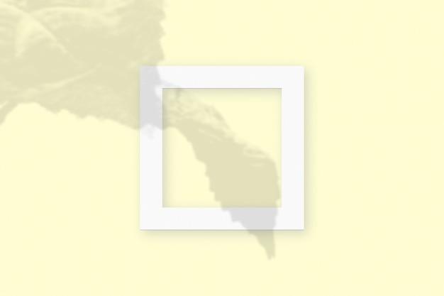 黄色のテーブルの背景にテクスチャの白い紙の正方形のフレームに野菜の影を重ねたモックアップ。