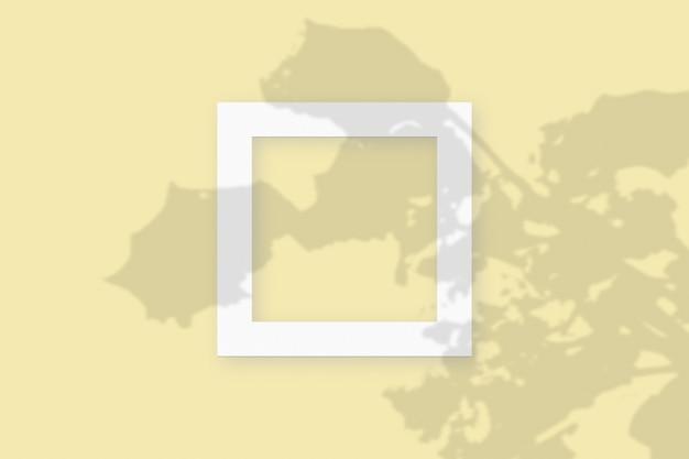 Мокап с растительными тенями, наложенными на квадратную рамку из текстурированной белой бумаги на желтом фоне стола.