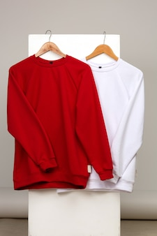 Mockup of womens red and white sweaters on simple background