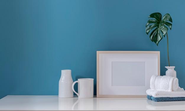 Мокап деревянной рамы с полотенцем и керамической вазой на белом столе