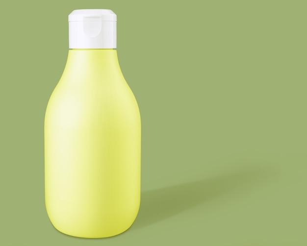 Макет желтой биоразлагаемой пластиковой косметической бутылки на зеленом фоне. вид спереди и пространство для копирования