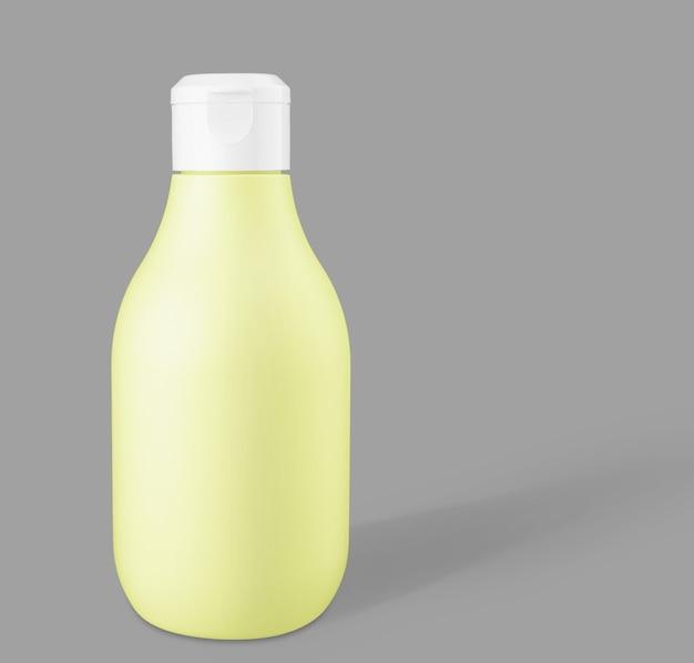Макет желтой биоразлагаемой пластиковой косметической бутылки на модном сером фоне. вид спереди и пространство для копирования