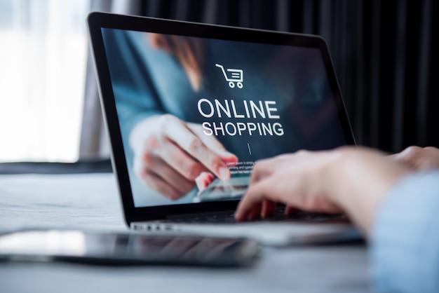 Концепция электронной коммерции и онлайн покупок, рука женщины используя компьтер-книжку (вебсайт mockup) и держащ кредитную карточку для делать покупки оплата онлайн дома.