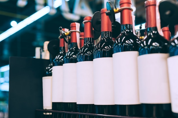 Mockups of glass bottles with wine on a supermarket counter.
