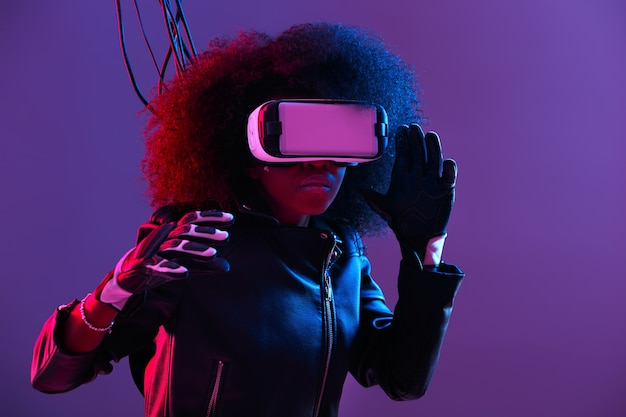 Модная кудрявая темноволосая девушка в черной кожаной куртке и перчатках использует очки виртуальной реальности на голове в темной студии с неоновым светом. киберпанк персонаж