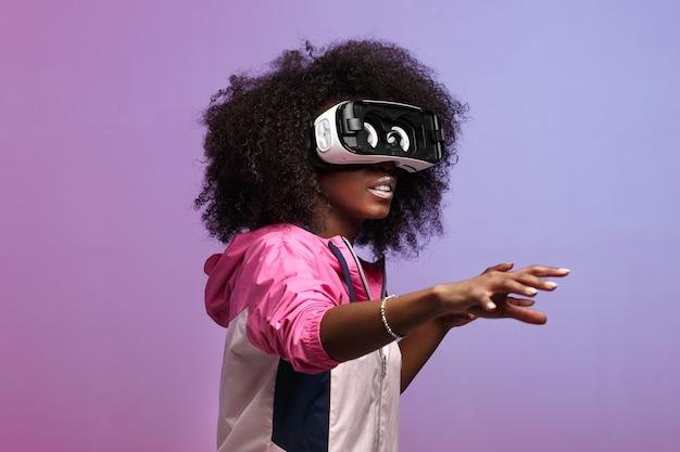 Модная молодая шатенка кудрявая девушка в розовой спортивной куртке использует очки виртуальной реальности в студии на неоновом фоне.