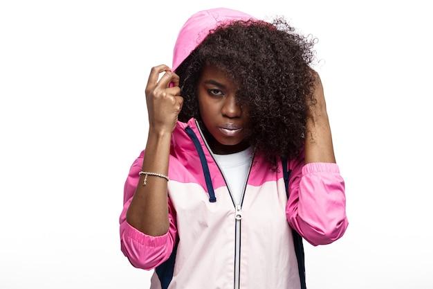 Молодая кудрявая шатенка в розовой спортивной куртке с капюшоном позирует на белом фоне в студии.