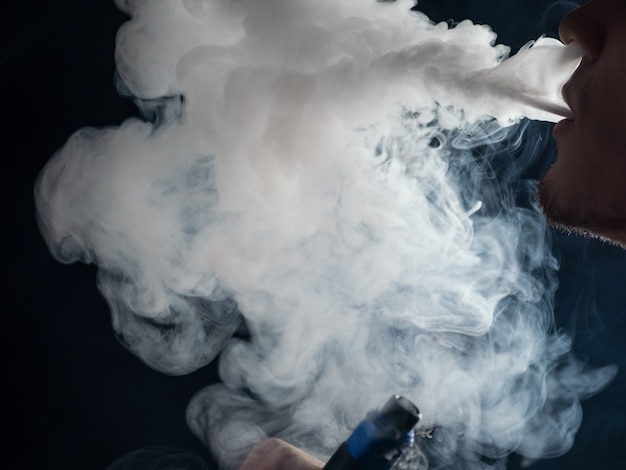 ベーパーマンのクローズアップは、蒸気の雲を吐き出します。電子タバコmod