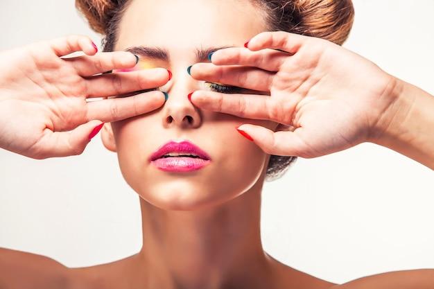 モデル、白い表面に明るい化粧と明るいマニキュアを持つ女性。スタジオ、美容、光沢、ニス。