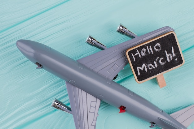 Model airplane on blue pastel color background. hello march on little nameplate.