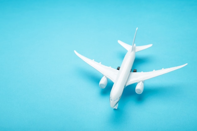Модель самолета на голубой стене пастельных тонов. концепция путешествия