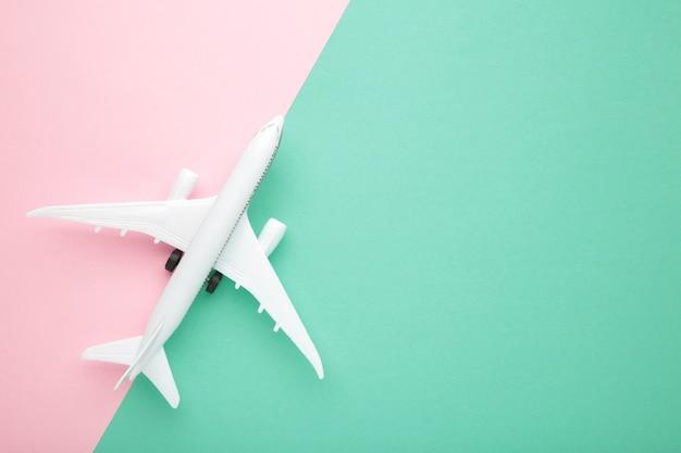 カラーパステルカラーの背景で飛行機をモデル化します。旅行のコンセプト。