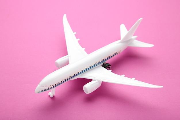 Модель самолета на розовом фоне пастельных тонов. концепция путешествия