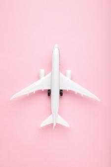 Модель самолета на розовой стене пастельных тонов. концепция путешествия