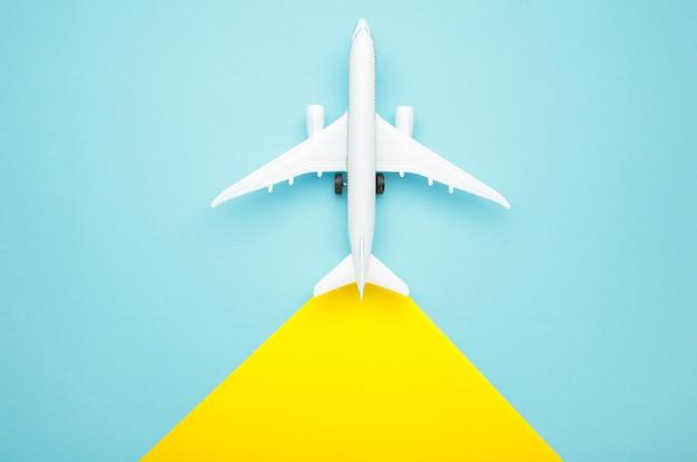 Модель самолета на желтом и синем фоне. концепция путешествия