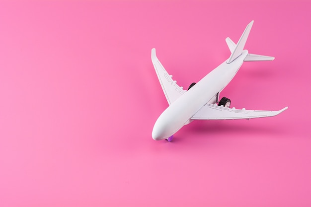 Model airplane on pink paper background.