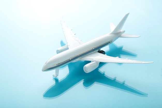 Модель самолета с тенью на голубой стене пастельных тонов. концепция путешествия
